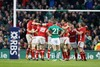 Wales players celebrate on the final whistle while Ronan O'Gara looks on